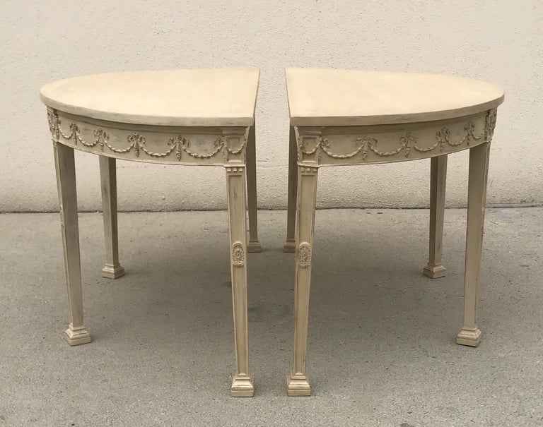 """Beautiful, pair of French late 19th century pair of painted and carved demilune console tables in the neoclassical style.  The console tables can come together to form a round table measuring 54"""" W x 52"""" L.  The tables have been re-freshed with"""