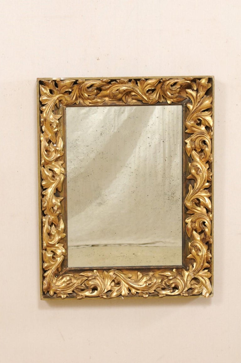 A French nicely carved giltwood mirror from the 19th century. This antique rectangular-shaped mirror from France features beautifully decorative, Rococo style, three-dimensionally carved leafy scrolls, set within the surround, framed with a flat