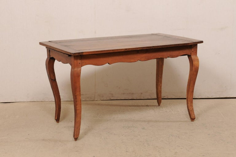 A French fruitwood table with single drawer and scalloped apron from the 19th century. This antique table from France features a rectangular-shaped top which overhangs a scallop-carved apron bellow which houses a single drawer at one short side and