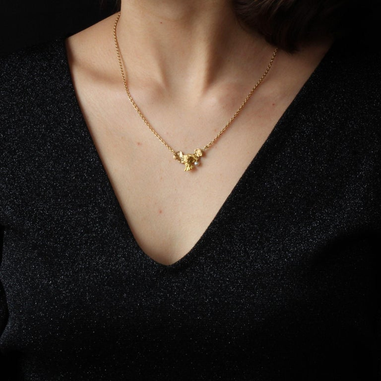 Pendant and its chain in 18 karat yellow gold, eagle head hallmark. Delightful antique necklace, it is constituted of a bird of prey in flight which holds in its beak a natural pearl. It is supported by a convict round mesh. Diameter of the pearl :