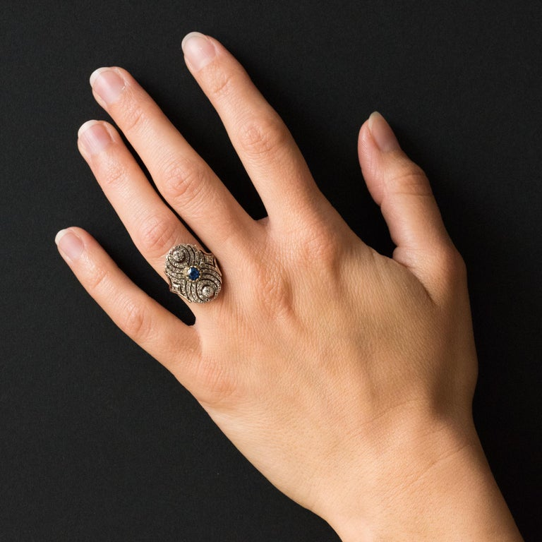 Ring in 18 Karats rose gold ring, eagle's head hallmark and silver. Lovely antique ring, it is set in the center with lowered claws of a cushion-cut sapphire and 2 antique brilliant-cut diamonds also with lowered claws. The whole openwork tray is