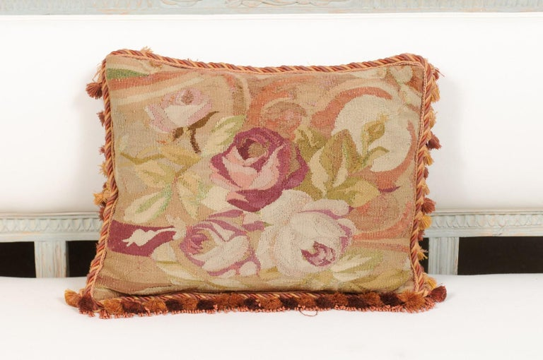 A French Aubusson tapestry pillow from the 19th century, with roses decor, cording and tassels. Born in central France during the 19th century, this Aubusson pillow features a charming bouquet of pink roses, seen in a horizontal format. Their pink