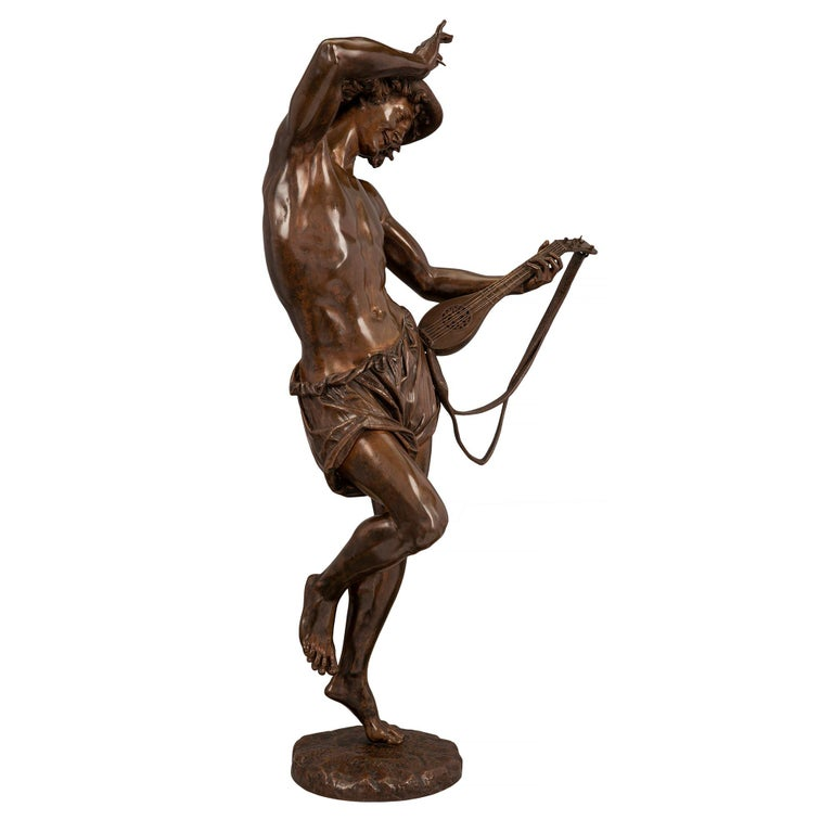 A stunning and high quality French 19th century Belle Époque period patinated bronze statue of a man dancing and playing a mandolin. The statue is raised by a circular base with a terrain design where the charming young man is dancing. He is wearing