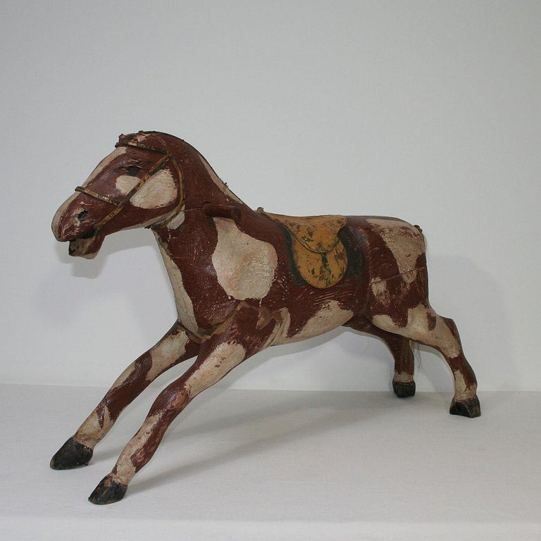 Beautiful and unique Folk Art wooden horse. Great form, wonderful original colors and leather saddle France, circa 1850-1900. Weathered and small losses.