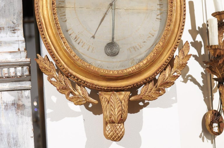 A French giltwood carved barometer from the 19th century, with eagle and laurel wreath motifs. Born in France during the 19th century, this barometer features an oval carved frame topped with an exquisite crest, adorned with a majestic eagle resting