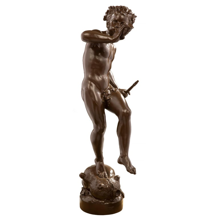 A charming and highly detailed French 19th century cast iron statue of a young boy playing the horn and holding a flute, signed 'A. Durenne, Paris'. The statue is raised by a circular base and is standing on a bagpipe. The whimsical and joyous boy