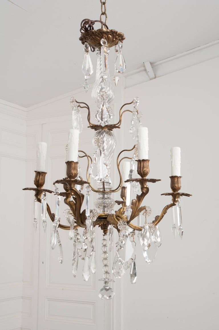 A stunning crystal and brass Louis XV style chandelier made in France, circa 1890. The six-light fixture is a fanciful combination of cut crystals and styled brass that form the dazzling antique. The brass frame is cast in the whimsical Louis XV