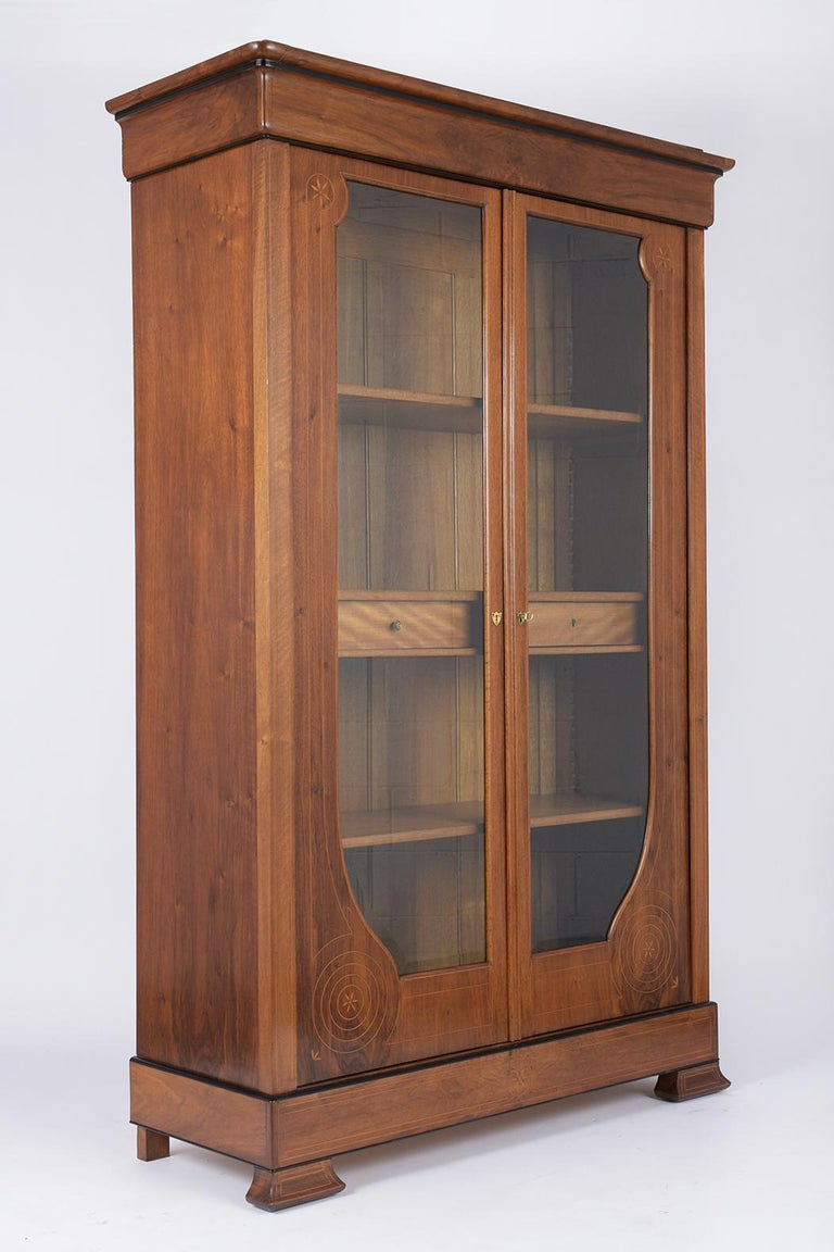 This French 19th century Empire bookcase has been completed restored, is made out of walnut wood with its original walnut color and has a newly waxed and polish patina finish. This bookcase features carved molding along the top/bottom, two large