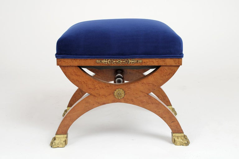 This French 19th century Empire style stool is made out of maple wood covered with a beautiful exotics burl veneer and has been professionally restored. This petite stool has been newly upholstered in blue velvet fabric with double piping detail.