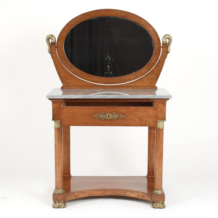 This French 19th century Empire style vanity table is made out of maple wood and is covered in a burled veneer with remarkable bronze accents decorations. This vanity has been restored and has kept its original color finish only having been waxed