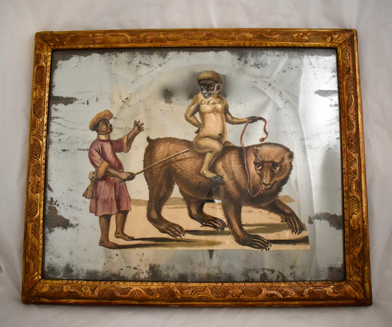 A unique 19th century French exotic themed, hand painted, decoupaged and mirrored depiction of an animal trainer and his monkey riding the back of a bear. One of a pair offered separately, as shown in the last photo.   The paper figural scene is cut