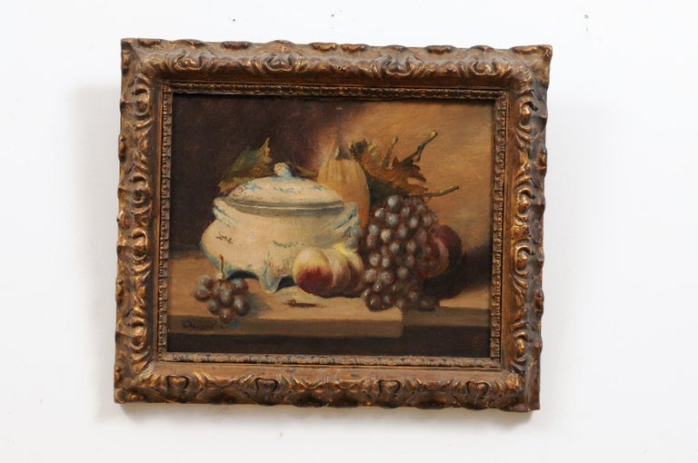A French framed signed oil on canvas painting from the 19th century, depicting fruits and porcelain. Created in France during the 19th century, this framed still-life captures our attention with its depiction of mouth-watering peaches and grapes