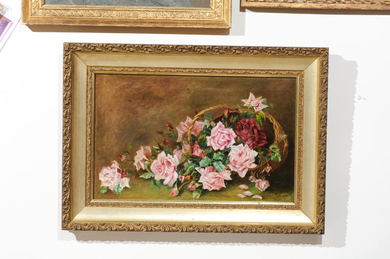 A French framed oil on canvas floral painting from the 19th century, depicting roses. Born in France during the 19th century, this exquisite oil on canvas painting features a delicate bouquet of pink roses falling on a tabletop from a tipped over