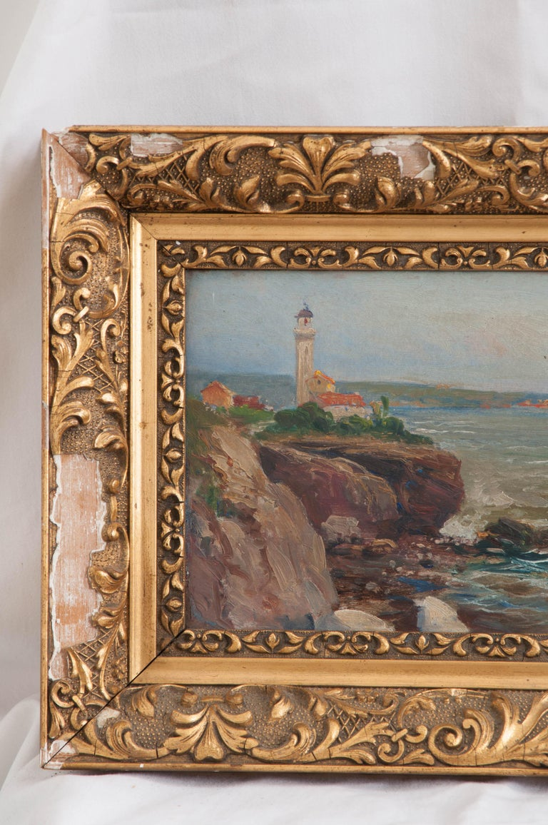 French oil painting on board of a seaside and lighthouse is surrounded by a distressed and decorative plaster, gilt frame. Signed by the artist, G. Cogneen.