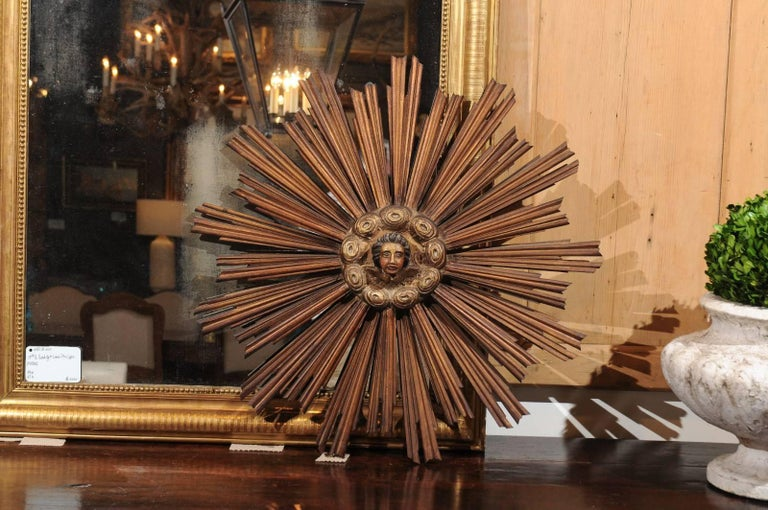 A French gilded and painted starburst wall decoration with carved angel face from the 19th century. This lovely starburst ornament features a carved and painted angel face sitting above two petite wings, surrounded by a ring of stylized clouds. This