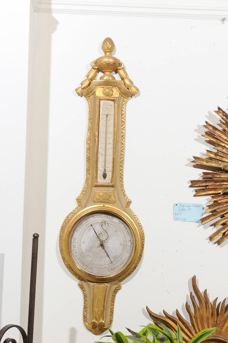 A French 19th century painted and gilt wooden barometer thermometer with carved urn crest. This French barometer features an exquisite crest, carved with a pinecone topped urn and flanked with a delicate swag. A twirling sun motif sits just above