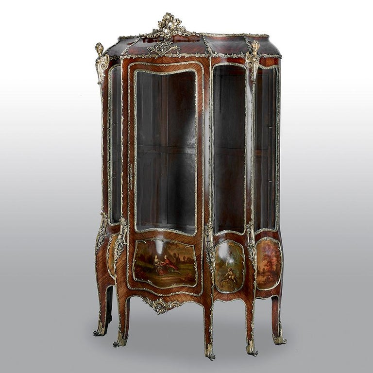 This fine and large Rococo style vitrine cabinet is crafted in kingwood, in a bombe form and features a large central panel flanked by four concave and convex panels. Below the glass there are five fine gilt-bronze-framed Vernis Martin panels.