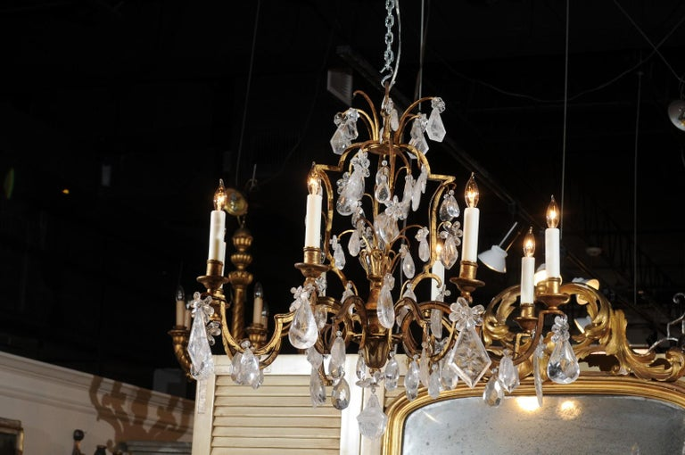 A French gilt iron eight-light chandelier from the 19th century, with Madagascar rock crystals. Born in France during the politically dynamic 19th century, this exquisite eight-light chandelier features a gilt iron armature, supporting several tiers