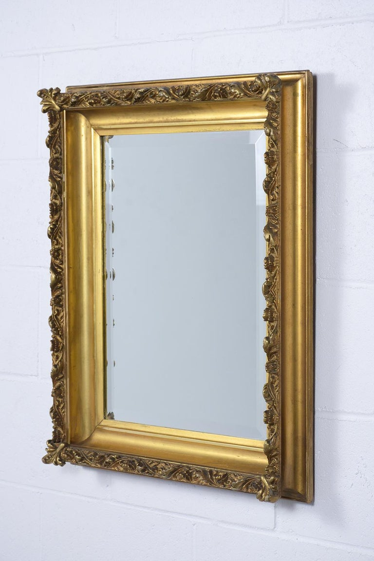 An extraordinary French antique Henry II wall mirror featuring a giltwood carved frame and rectangular bevel mirror in the center that is fully reflective. This elegant 19th-century gilt mirror is ready to be used and displayed for years to