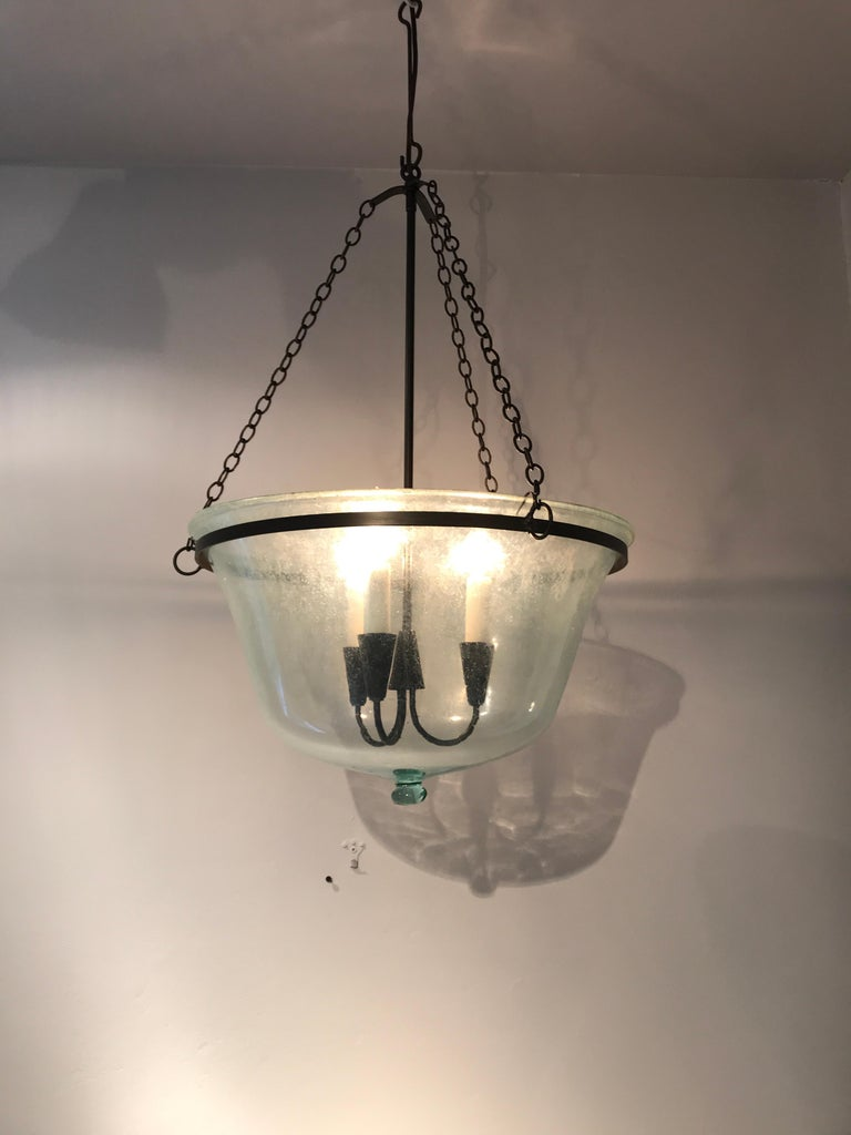 We have always had a thing for hand blown French garden cloches that come in two configurations: Bell form and melon form. This one is a melon cloche (a little shorter and wider than a bell cloche) and it has been converted into a hanging light with
