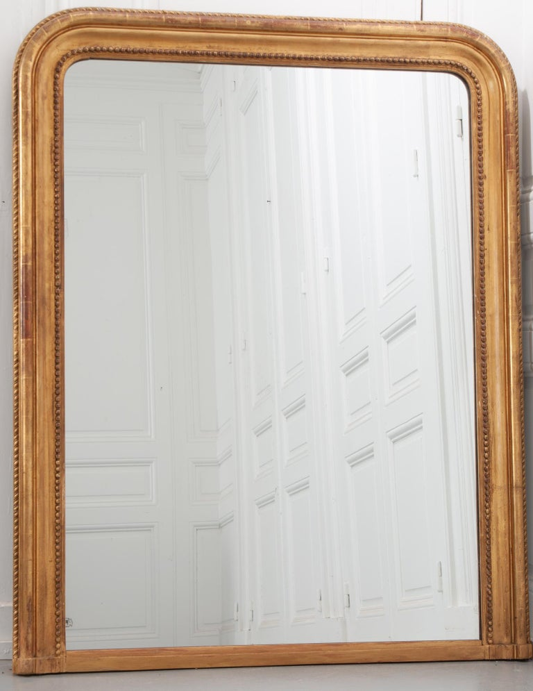 This is a French 19th century Louis Philippe gold gilt mantle mirror with its original mirror plate. It has some aging and surface scratches in the mirror plate. The mirror's frame is ornamented with wonderful twisted rope and beaded pearl motifs.