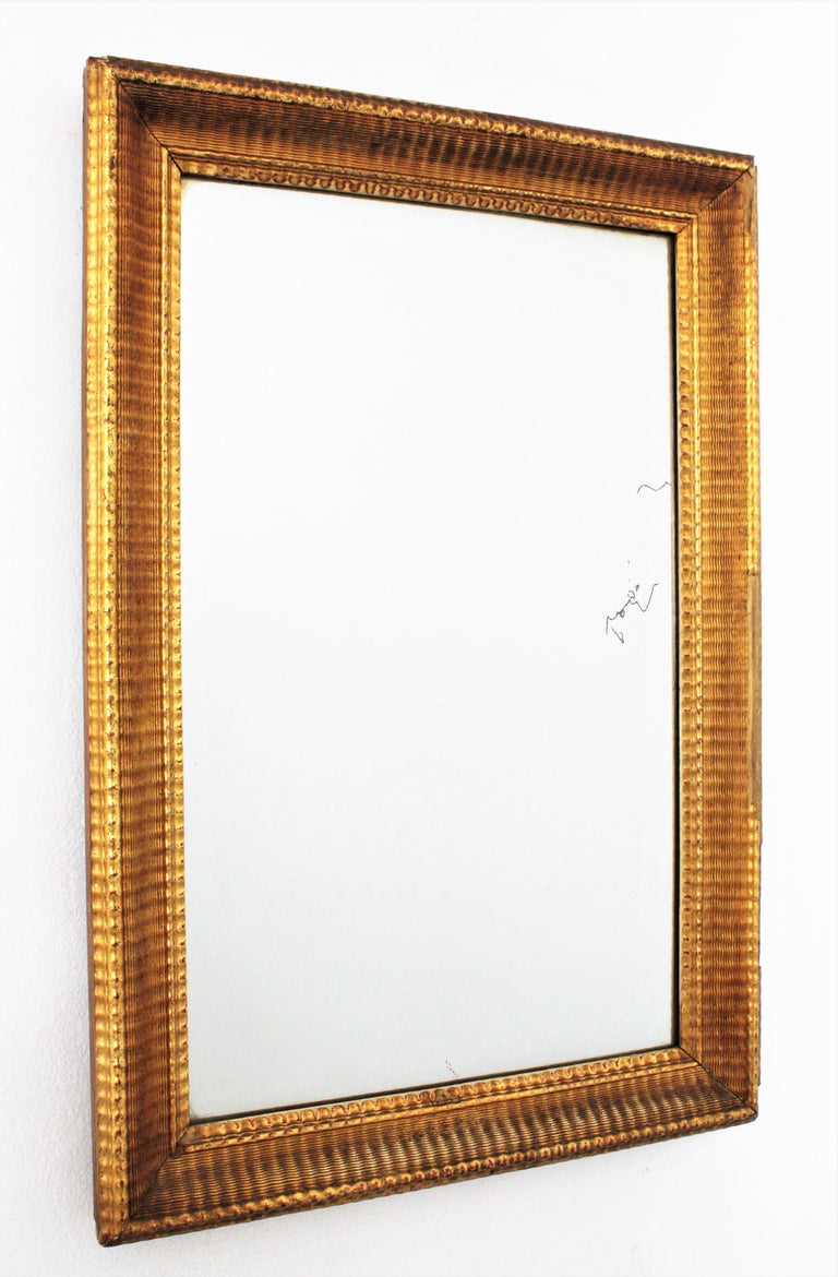 Amazing Louis Philippe period mirror with a finely ribbed carving frame and gold leaf finish. France circa 1860. Elegant, strong and soung, this mirror has a gorgeous original aged patina. It has some losses on the frame, but they don't rest