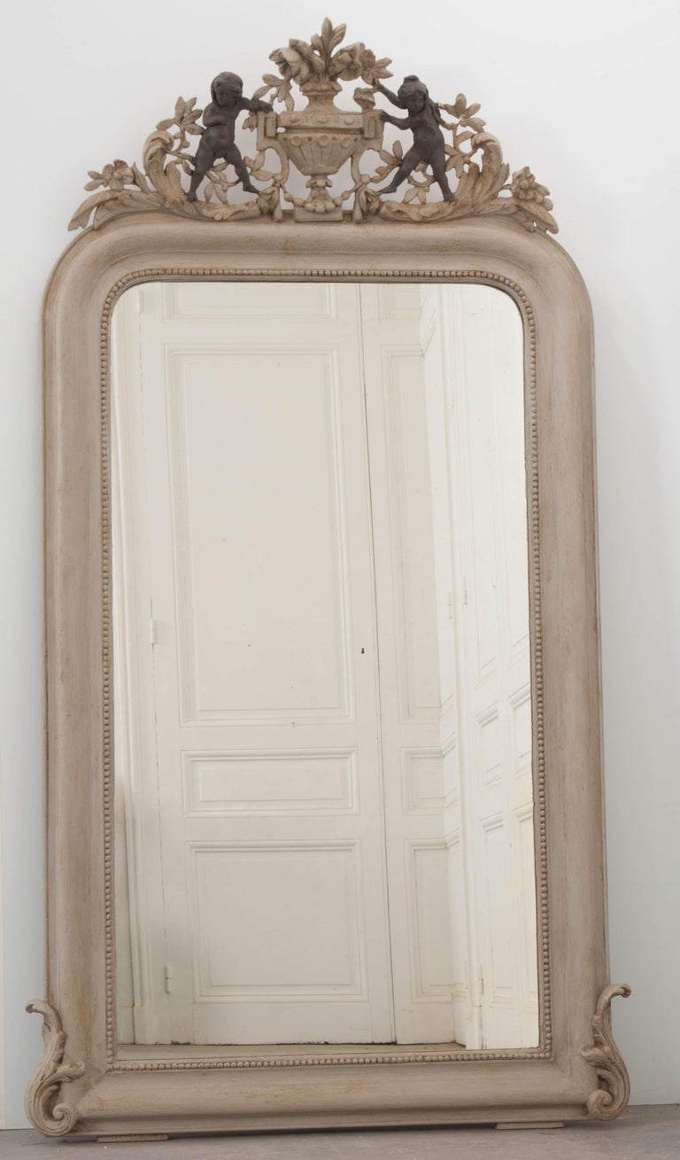 This stunning grisaille 19th century Louis Philippe mirror, circa 1840, is from France and features a crest with central urn flanked by a air of putti amongst flowering vines. The beaded frame, with S-scrolls at the lower corners, encases a