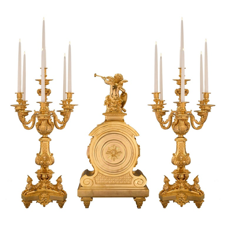 An extraordinary and high quality French 19th century Louis XIV St. ormolu three-piece clock and candelabras garniture set. Each raised by square tapered fluted feet with fine acanthus leaf sabots. The clock displays a magnificent family crest
