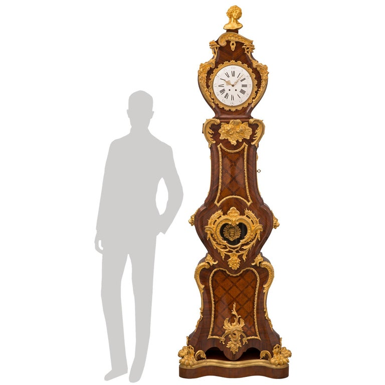 A spectacular and extremely high quality French mid 19th century Louis XV st. kingwood, tulipwood, and ormolu grandfather clock. The clock is raised by a fine scalloped shaped kingwood base with a mottled wrap around ormolu band and handsome richly