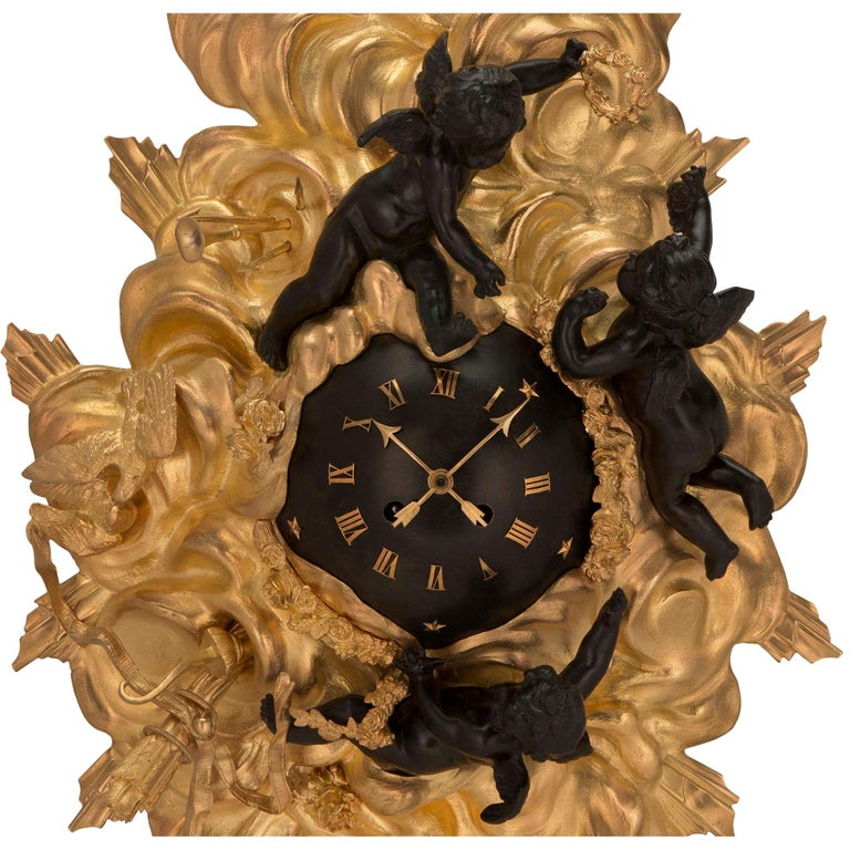 A beautiful French 19th century Louis XV st. ormolu and patinated bronze cartel clock. The clock displays a most elegant and decorative cloud like design with richly chased love birds, arrows, quivers, musical instruments and swaging floral garlands