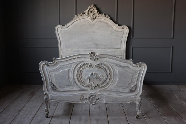 This French 19th century Louis XV style bed frame fits an XL twin mattress. It has a solid wood frame that is painted a pale light blue, and grey with a distressed finish. It has carved details on the headboard, footboard, and wooden rails. The legs
