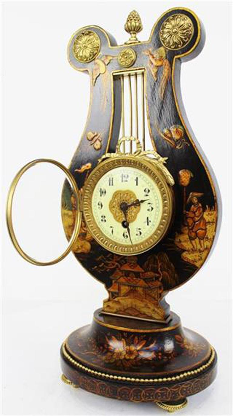 Rare 19th century French Louis XV style black chinoiserie lyre clock with raised decoration.  The case topped by embossed circular mounts and a bronze finial. The cream porcelain dial with black Arabic numerals with a decorative brass bezel