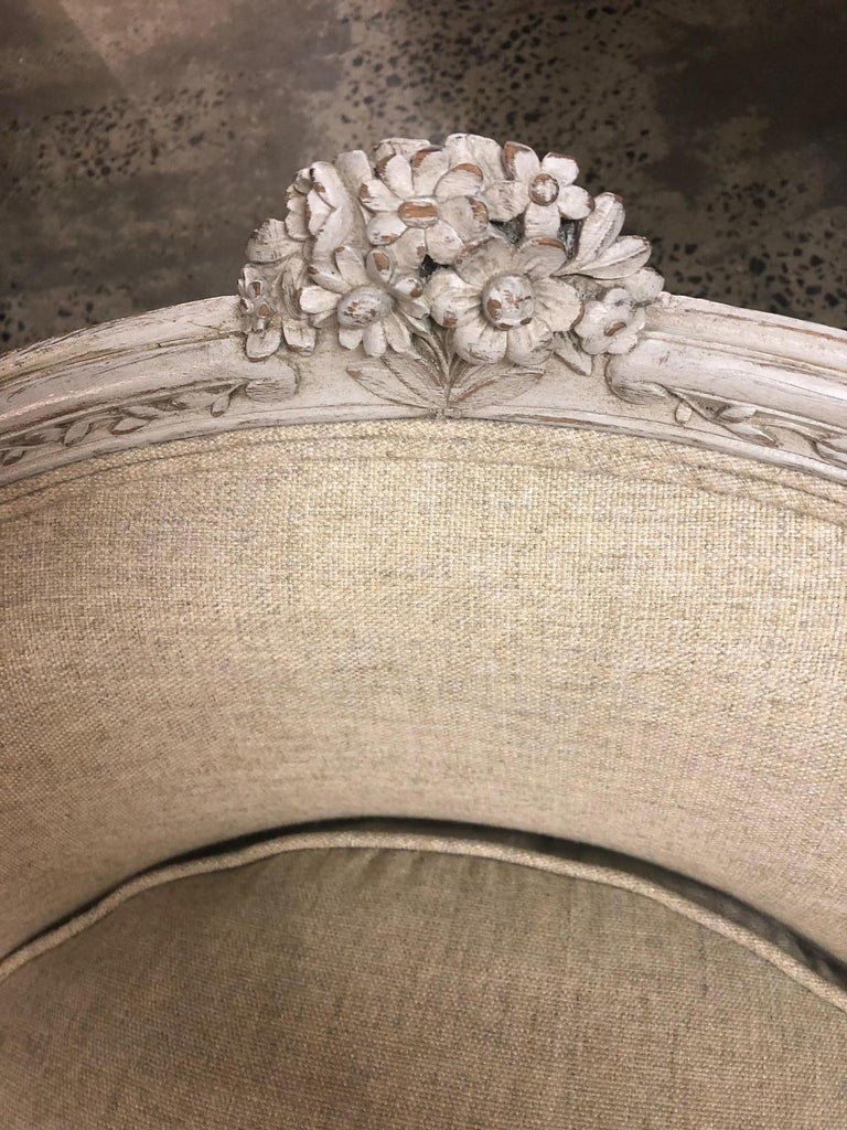 An oak and linen upholstered French 19th century Louis XV style Duchesse Brisee, the seat with slightly concave back, the lime-washed back rail with central carved rosette, to padded arm rests, the central footstool with conforming carving, the