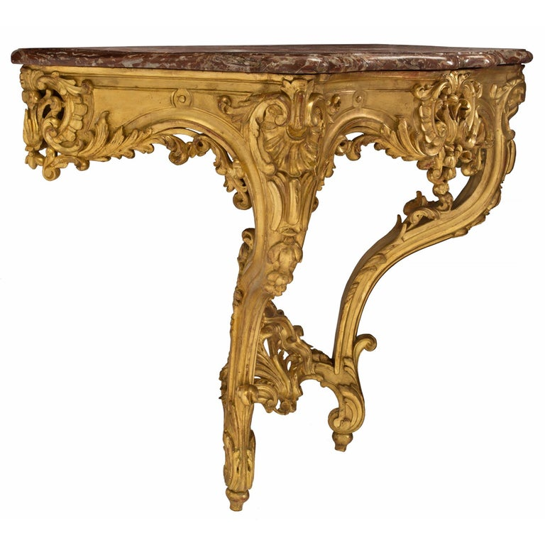 An elegant French 19th century Louis XV style giltwood and marble wall-mounted console. The console is raised by fine toupie shaped feet below elegant cabriole legs adorned with richly carved acanthus leaves and floral movements. The legs are