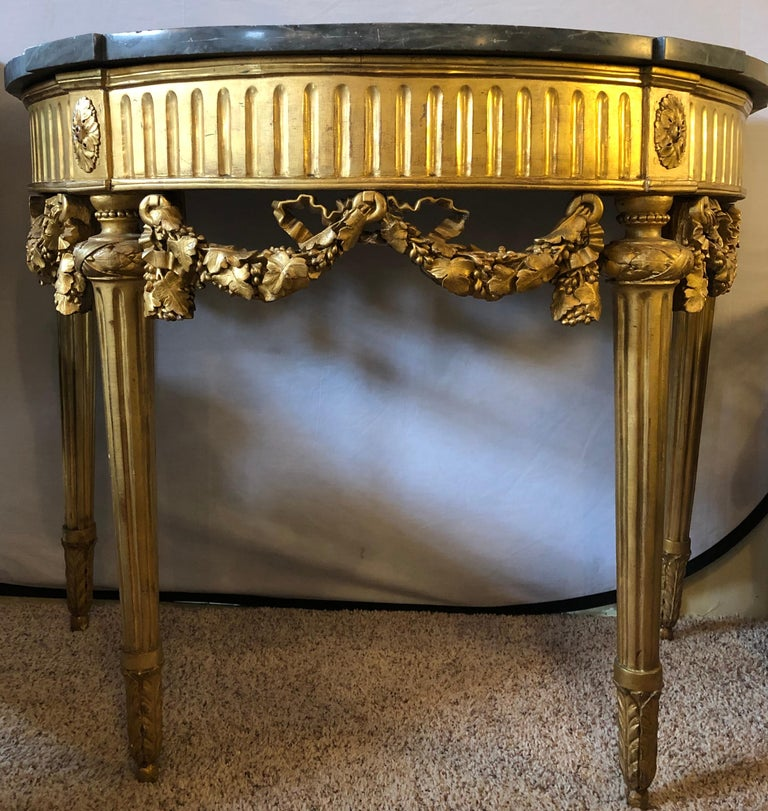 French 19th century Louis XVI console with marble top. This fine gilt console is simply stunning with its gray marble top supported by a ribbon and bow carved leaf design apron and group of four carved tapering legs, mid-late 19th century.