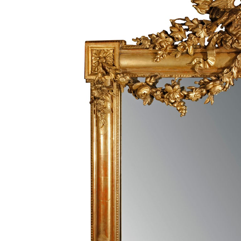 A very attractive French 19th century Louis XVI giltwood mirror. This rectangular mirror has corner block rosettes. On each side is an impressive protruding basket filled with fruit and foliate hanging by a bow. At the bottom is a pair of berried