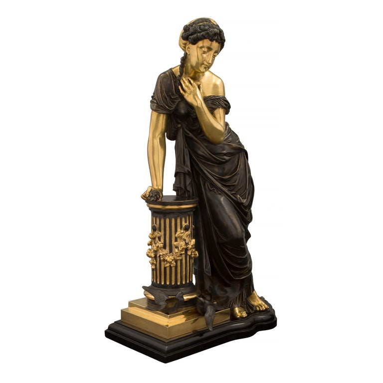 A most elegant French 19th century Louis XVI style patinated bronze and ormolu statue of a beautiful maiden, attributed to Pierre Louis Detrier. The statue is raised by a lovely scalloped shaped base with a mottled border where the beautiful lady