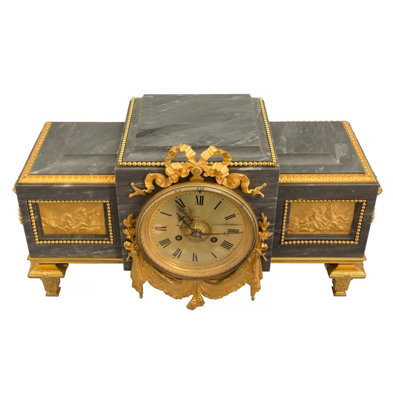 An elegant French 19th century Louis XVI style Gris St. Anne marble and ormolu pedestal clock. The rectangular-shaped pedestal clock is raised by ormolu topie shaped legs below a mottled band. The protruding center has a metal dial with roman