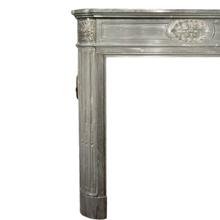 A charming French 19th century Louis XVI style small scale Gris St. Anne marble mantel. The mantel is designed with two fluted jambs and large ormolu rosettes at each side. At the molded edge facade is a carved rosette and block rosettes at each cut