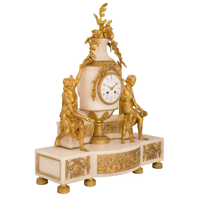 A spectacular French 19th century Louis XVI St. white Carrara marble and ormolu clock, signed Samuel Marti. The clock is raised by six beautiful circular ormolu feet with fine fluted and beaded designs. The white Carrara marble base displays a most
