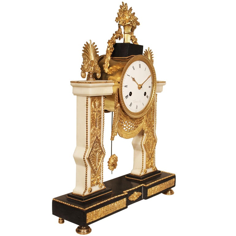 An important French 19th century Louis XVI style white Carrara marble and ormolu clock signed Vaillant. The clock is raised on a Black Belgium marble base with ormolu topie supports. Above two columns with finely chased floral ormolu mounts and