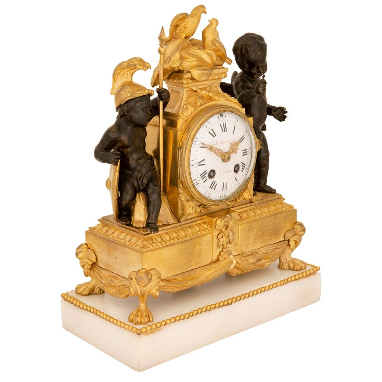 A high quality and extremely charming French 19th century Louis XVI st. white Carrara marble, ormolu and patinated bronze clock, signed Briscard, à Paris. The clock is raised by a rectangular white Carrara marble base with a fine beaded wrap around