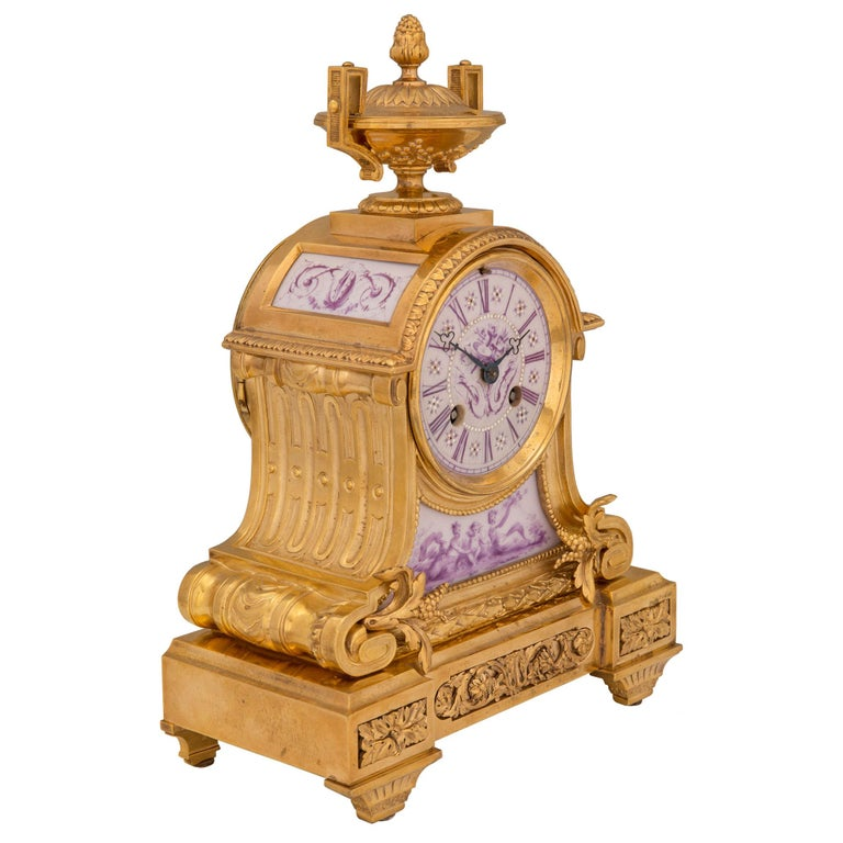 An elegant French 19th century Louis XVI St. ormolu and porcelain clock. The small scale clock is raised by fine tapered fluted legs below striking richly chased block rosettes centering a lovely pierced rinceaux shaped fitted ormolu plaque. The