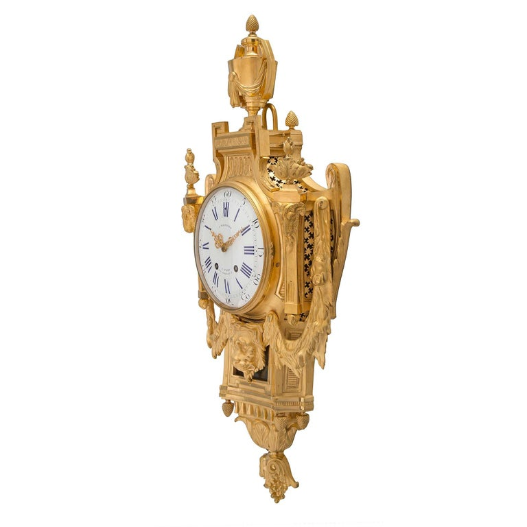A stunning and high quality French 19th century Louis XVI st. ormolu cartel clock, by L. Marchand. The clock has a fine berried and foliate bottom inverted finial and finely etched leaves, below four acorn finials. Above is a handsome and impressive