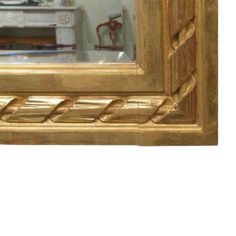 A very attractive French late 19th century Louis XVI st. rectangular shaped giltwood mirror, with original beveled mirror plate. The mirror has a very impressive moulded giltwood frame, decorated by a large and richly stylized ribbon design central
