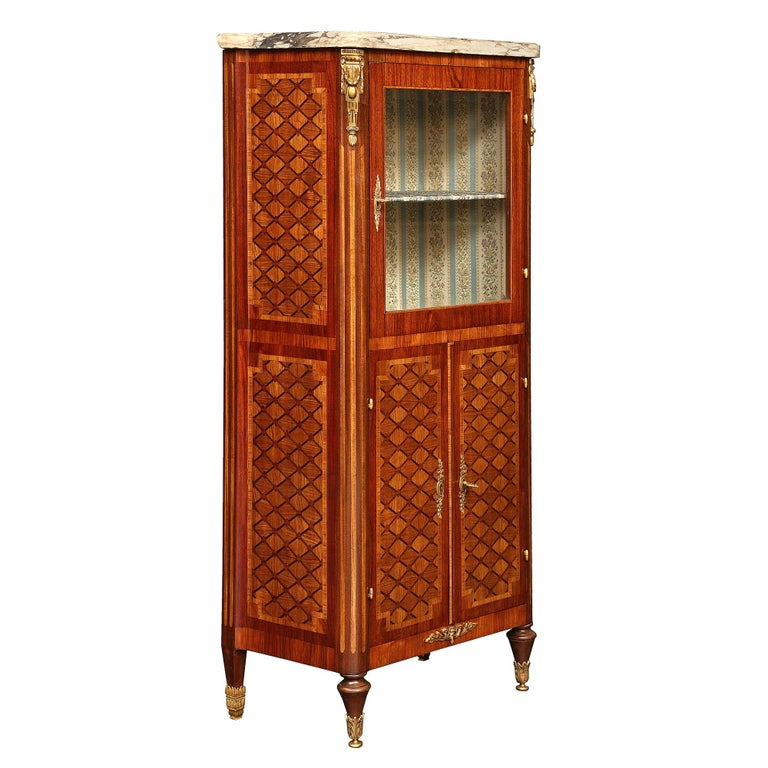 A high quality French 19th century Louis XVI style tulipwood and kingwood inlaid vitrine. Raised by toupie shaped supports in the front and square tapered ones in the back, all with ormolu sabots. The straight apron is centered by a stunning ormolu