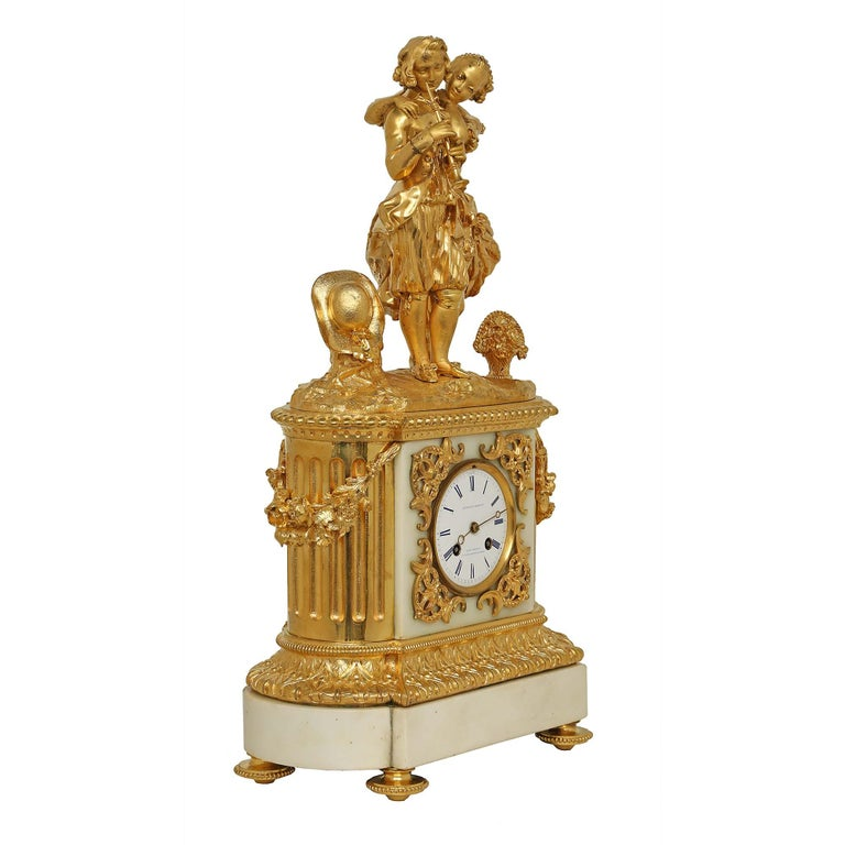 A charming mid-19th century French Louis XVI style white Carrara marble and ormolu clock, collaborated and signed by clockmaker Vittoz et Cie and Bronzier Larroue à Paris. The clock is raised by four chased topie supports below the white Carrara