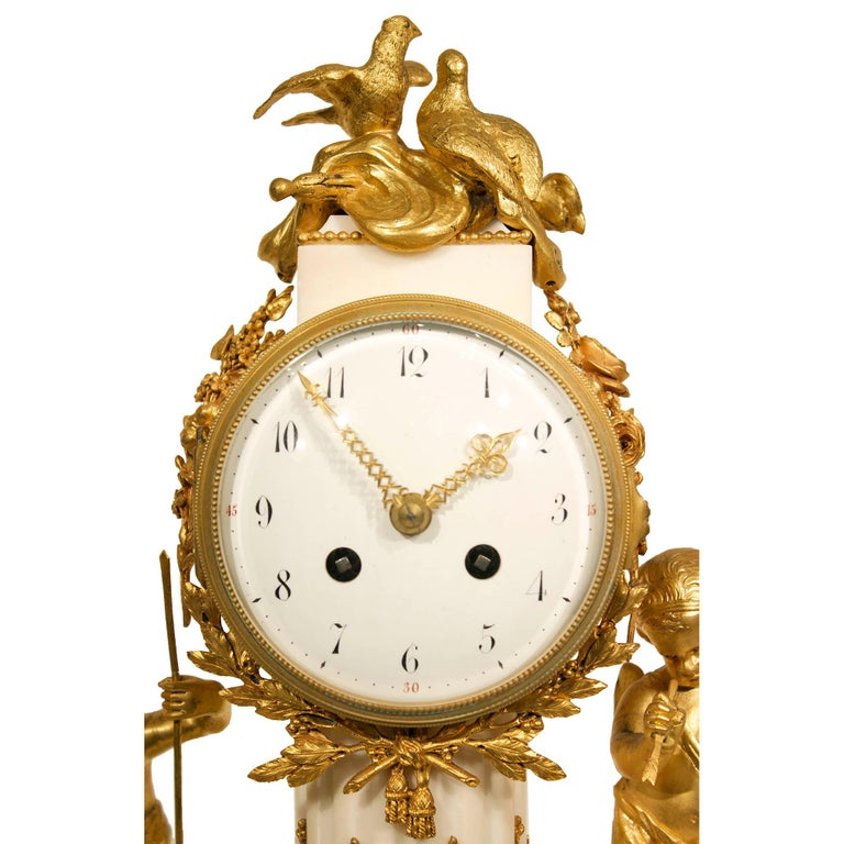 An exquisite French 19th century Louis XVI style white Carrara marble and ormolu clock. The clock is raised by ormolu toupie shaped supports below a marble base with ormolu scrolling foliage and ormolu beaded row. Above is the central fluted marble
