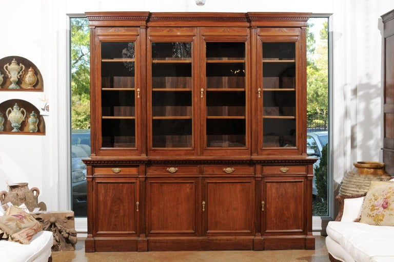 A French Louis XVI style blond mahogany bookcase from the 19th century, with glass doors, recessed center and pilaster motifs. Born in France during the 19th century, this elegant bibliothèque presents the stylistic characteristics of the Louis XVI