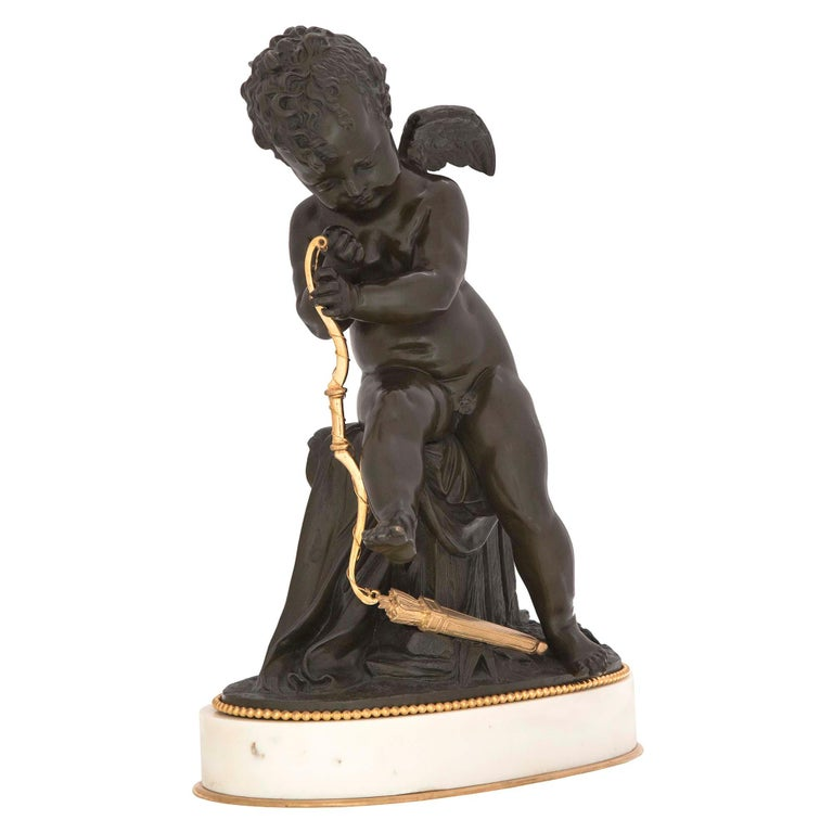 A high quality and most charming French 19th century Louis XVI style patinated bronze, ormolu and white Carrara marble statue signed Lemire. The statue is raised by an oval white Carrara marble base with a bottom ormolu fillet and a decorative